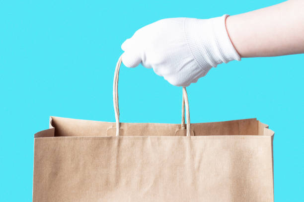 Female hand in a white glove holds brown cardboard bag, food delivery concept. stock photo