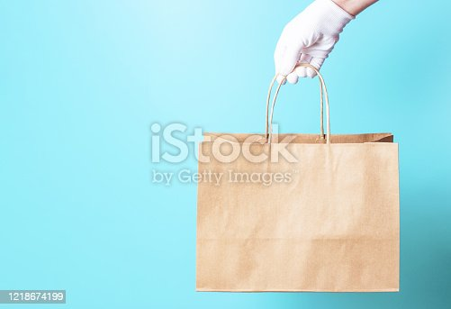 Female hand in a white glove holds a brown cardboard bag on a blue background, food delivery concept.