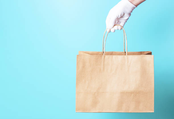 Female hand in a white glove holds brown cardboard bag on a blue background, food delivery concept. stock photo