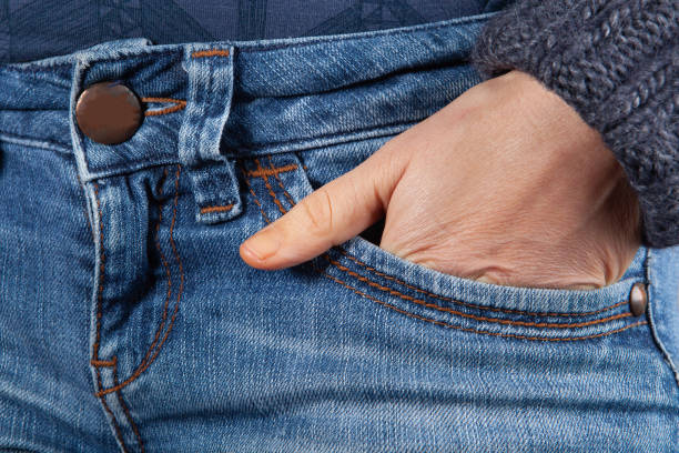 Female hand in blue jeans front pocket closeup Female hand in blue jeans front pocket closeup hands in pockets stock pictures, royalty-free photos & images