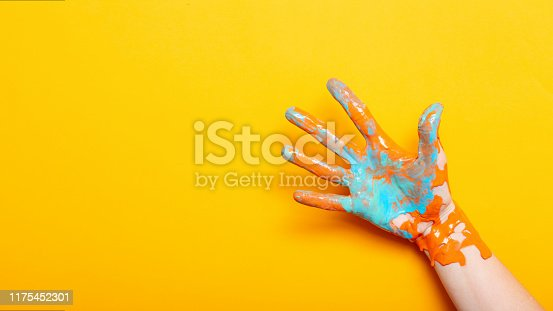 istock female hand in the paint color mixing on a yellow background, creative idea of advertising, palm gesture five 1175452301