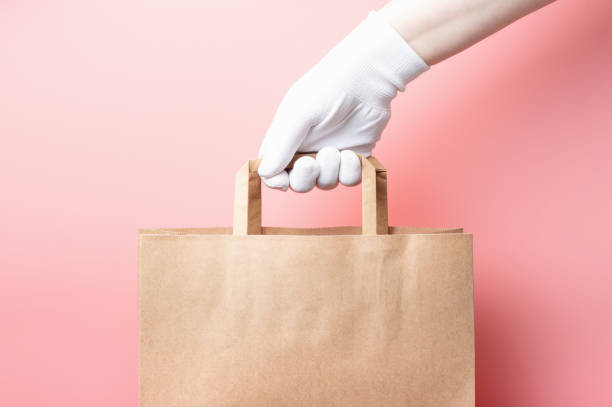 Female hand in white glove holds brown cardboard bag on a pink background, food delivery concept. stock photo
