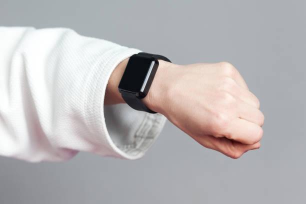 weibliche hand in weißen ärmel mit smartwatch zeigen pulsmesser. helthcare und technologie-konzept für den profisport. - wortarten bestimmen übungen stock-fotos und bilder