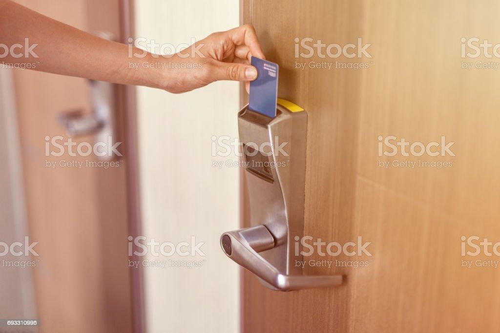 female hand insert room card key to open hotel room door stock photo