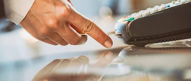 feminino mão ao inserir o cartão de crédito em um leitor - inserindo - fotografias e filmes do acervo