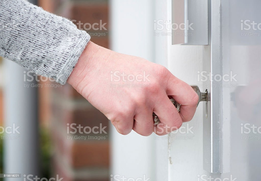 Female hand inserting key in door stock photo