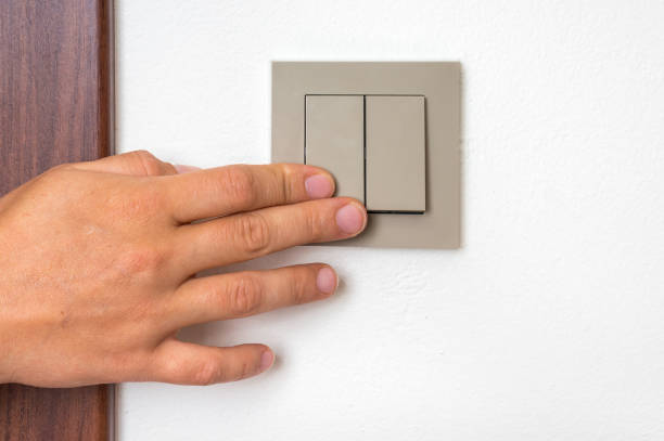 Female hand is turning on or off interior light switch stock photo