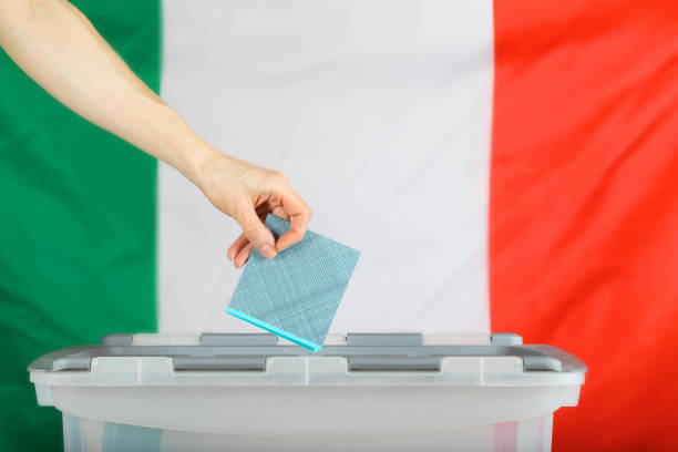 Female hand keeps ballot over ballot box. stock photo