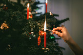 female hand lighting red candle on christmas tree at christmas eve