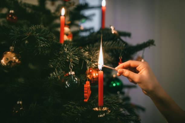 female hand lighting red candle on christmas tree stock photo
