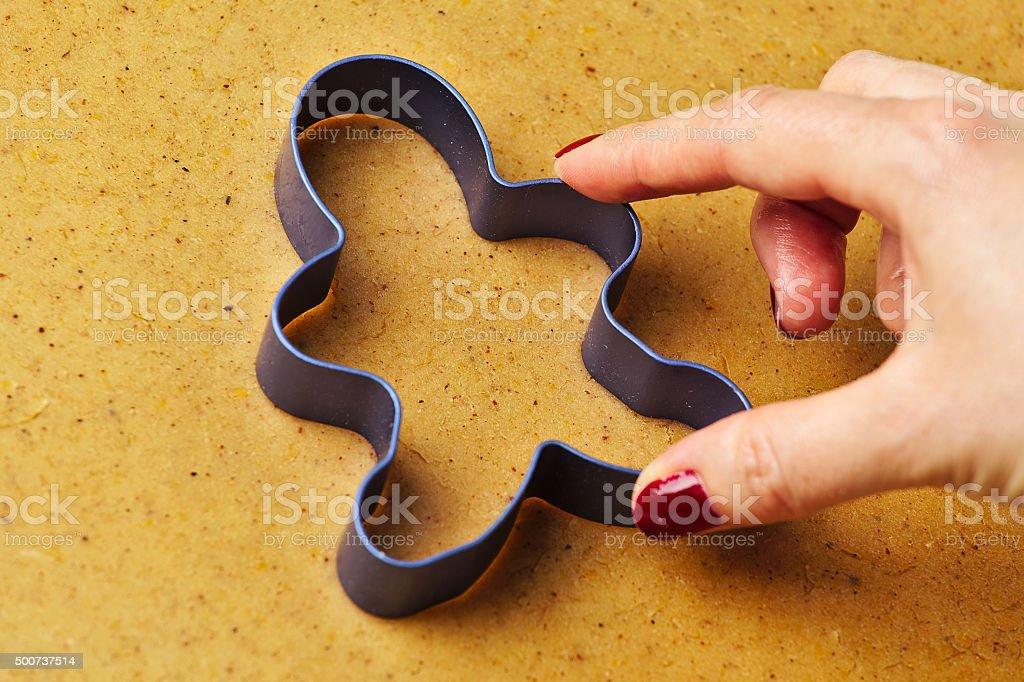 Female hand making christmas gingerbread men cookies stock photo