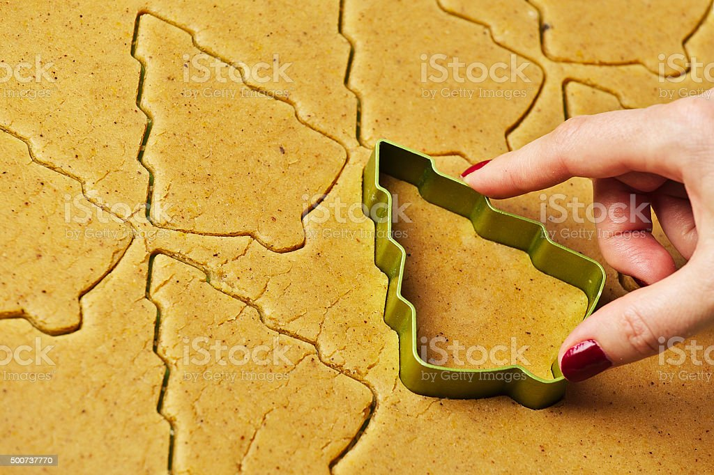 Female hand making christmas tree gingerbread cookies stock photo