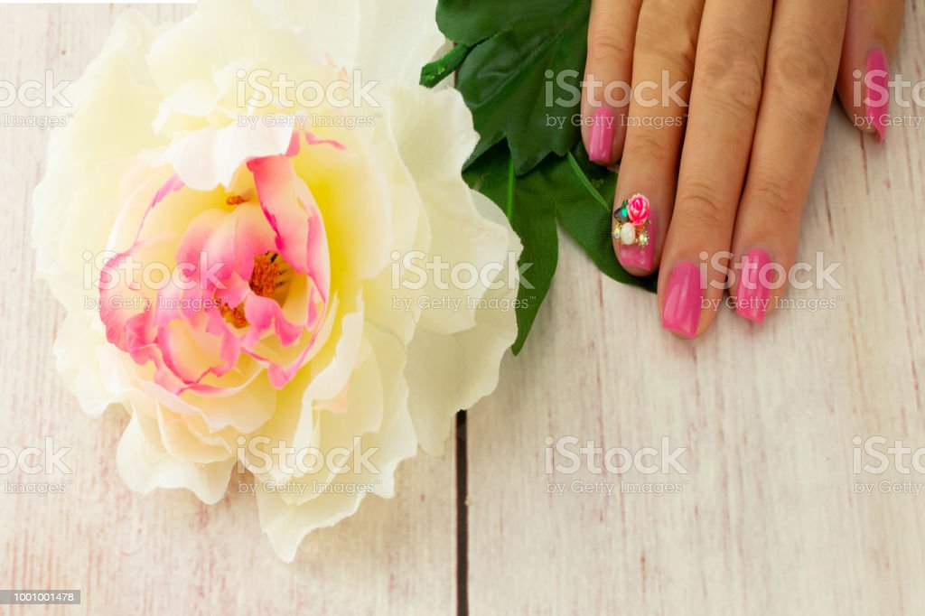 Female hand of woman, pink manicured on nails with a blossom of white...