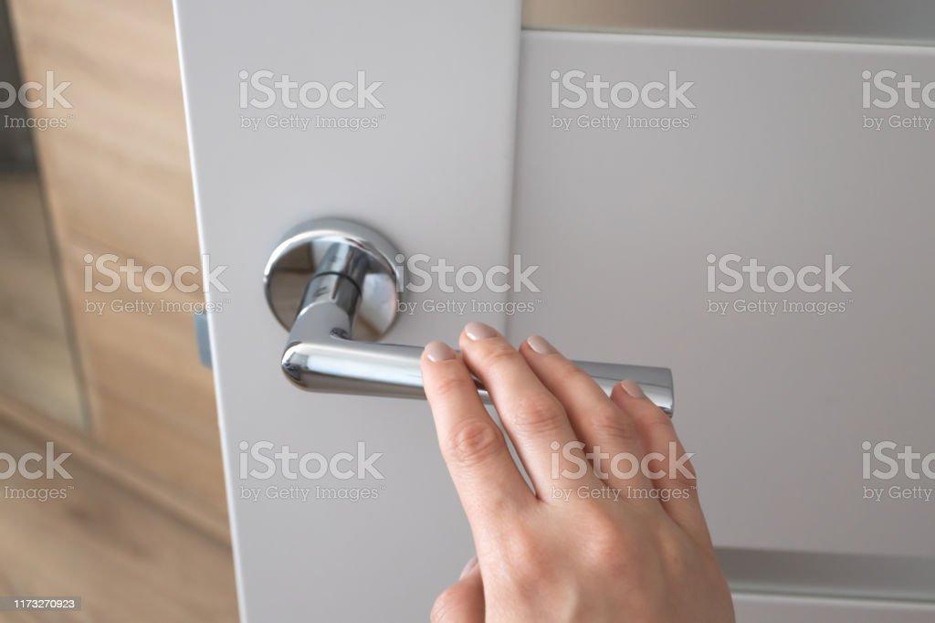 Weibliche Hand auf Metall-Türgriff. Modernes Interieur - Lizenzfrei Abschließen Stock-Foto