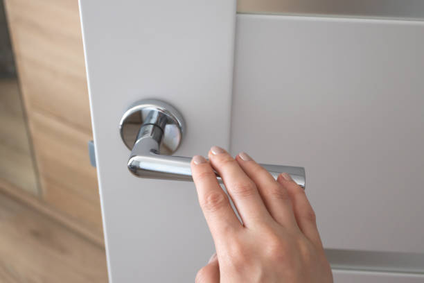 mão fêmea no punho de porta do metal. detalhe interior moderno - maçaneta manivela - fotografias e filmes do acervo