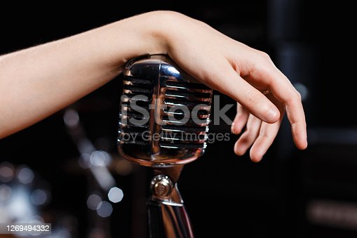 Female hand on retro microphone close-up