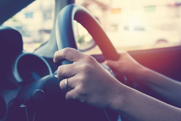 Female hand on steering wheel. Travel and safty concept. stock photo