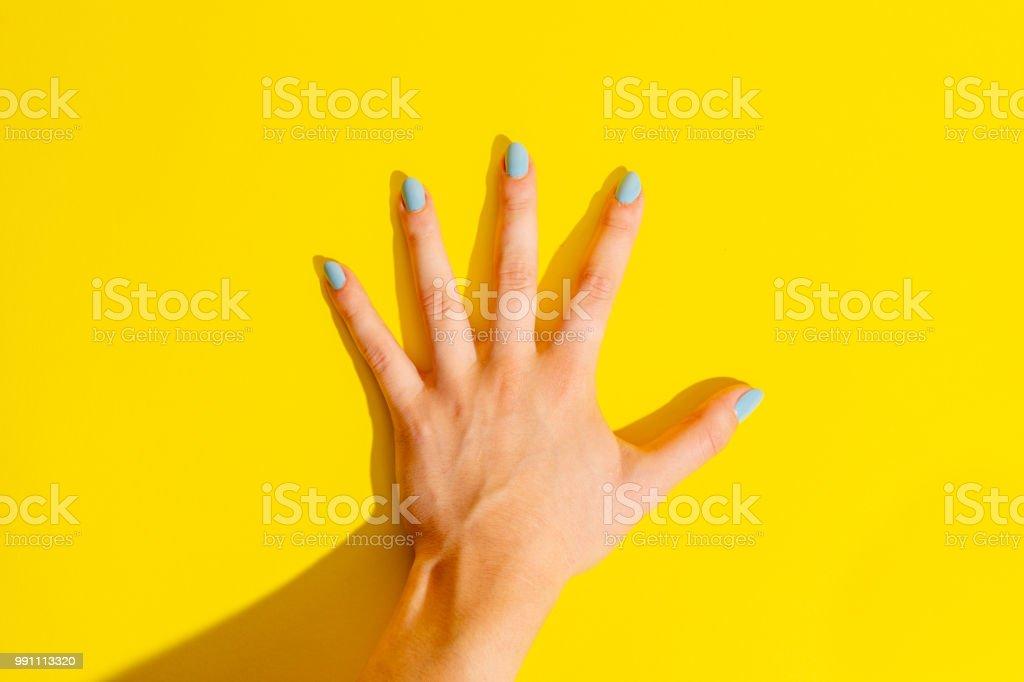 Female Hand on Yellow Background stock photo