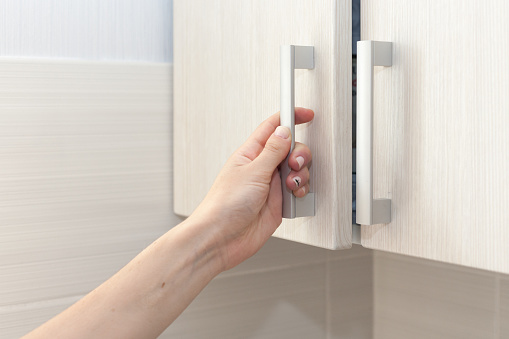 Female hand open the cupboard doors, close up