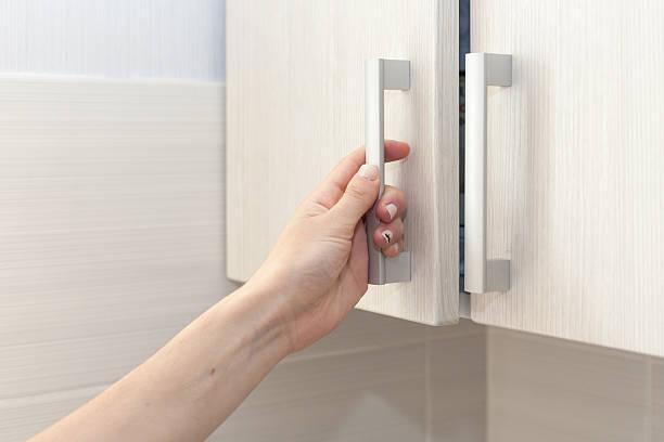 female hand open the cupboard doors, close up - griffe für küchenschränke stock-fotos und bilder