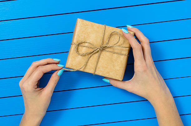 female hand opening gift box - blue yellow band bildbanksfoton och bilder