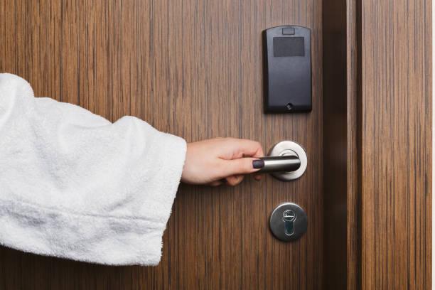 weibliche hand öffnen hotel zimmer türgriff - schlüssel dekorationen stock-fotos und bilder