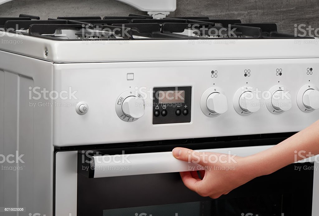 Female hand opening oven in white kitchen stove on gray foto stock royalty-free