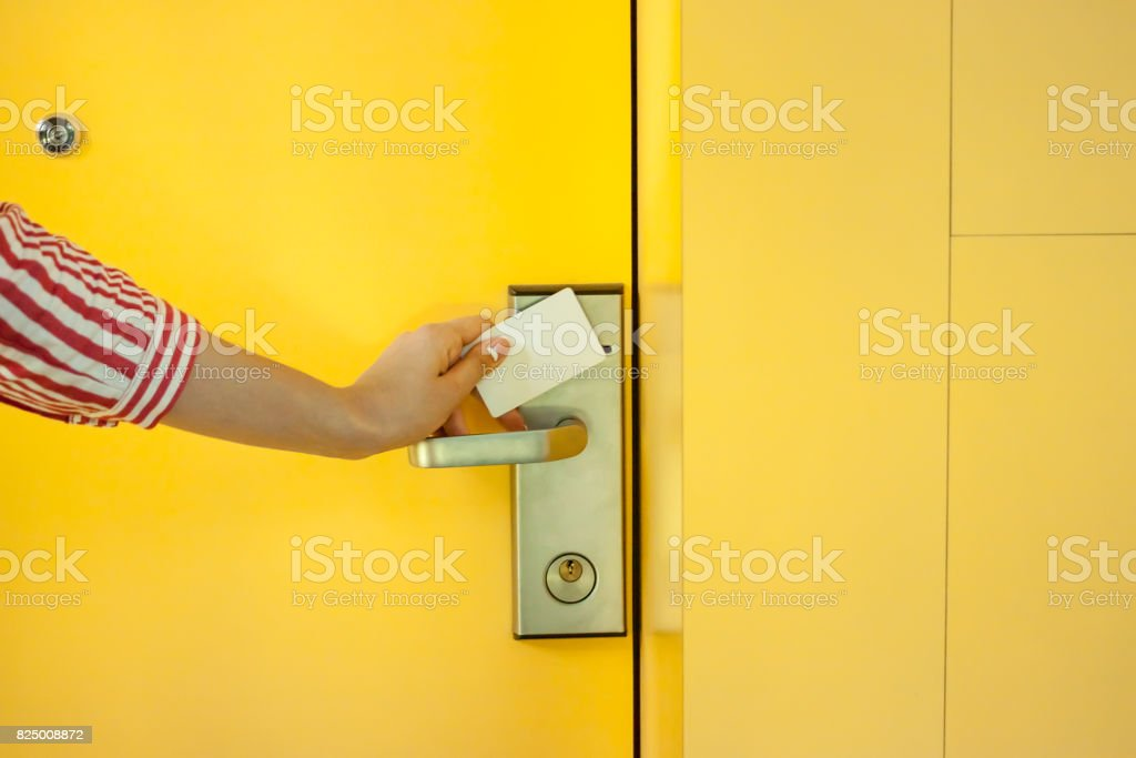 female hand opening yellow hotel door with card stock photo