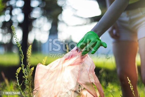 istock Female Hand Picking Up a Plastic Bag 1160025446