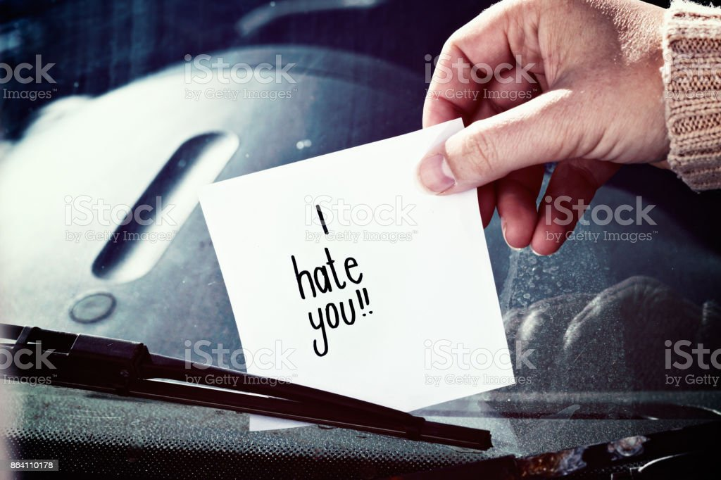 Female hand placing 'I hate you!' note on windscreen royalty-free stock photo