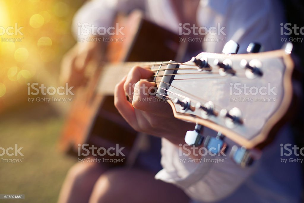 Female hand playing guitar outdoor stock photo