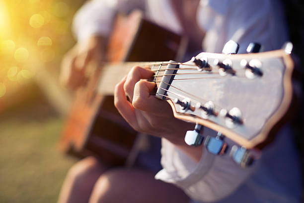 Female hand playing guitar outdoor - Photo