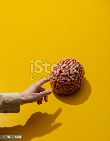 female hand points finger at brain on yellow background