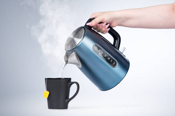 Female hand pours hot water from an electric kettle into a black mug, on light background. Female hand pours hot water from an electric kettle into a black mug, on light background. major military rank stock pictures, royalty-free photos & images