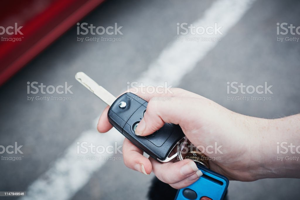 A woman\'s hand presses a button on a remote control to lock or unlock...