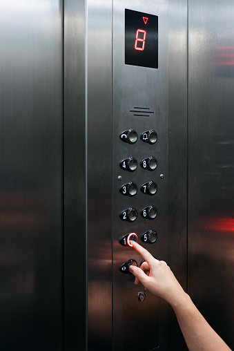 istock Female hand pressing elevator button going downward 938950316