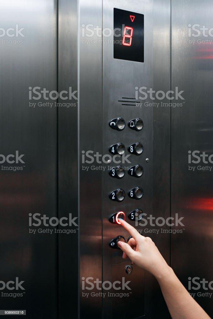 Mujer mano presionando botón del elevador yendo hacia abajo - foto de stock