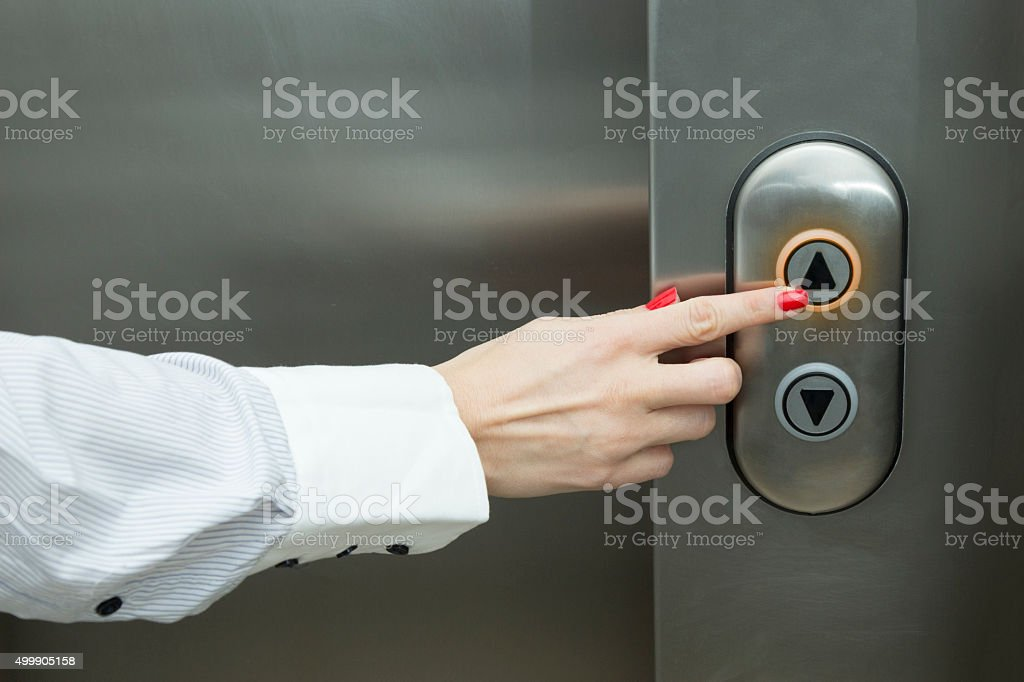 Female hand pressing elevator up button stock photo
