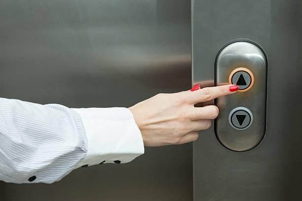 Mano de mujer planchado de ascensor de botón - foto de stock