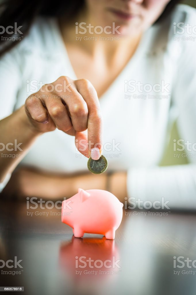 Female hand putting a coin into piggy bank. One EURO coin stock photo