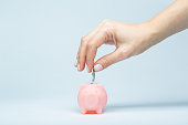 Female hand putting a coin into piggy bank