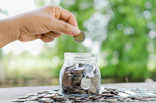 female hand putting money coins in jar concept and green nature background stock photo