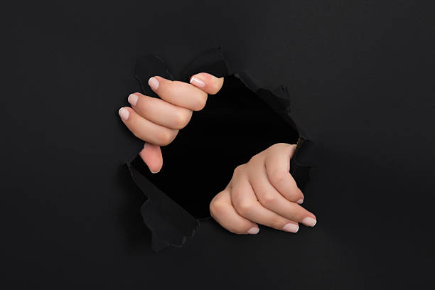 Female hand reaching through torn black paper sheet – Foto