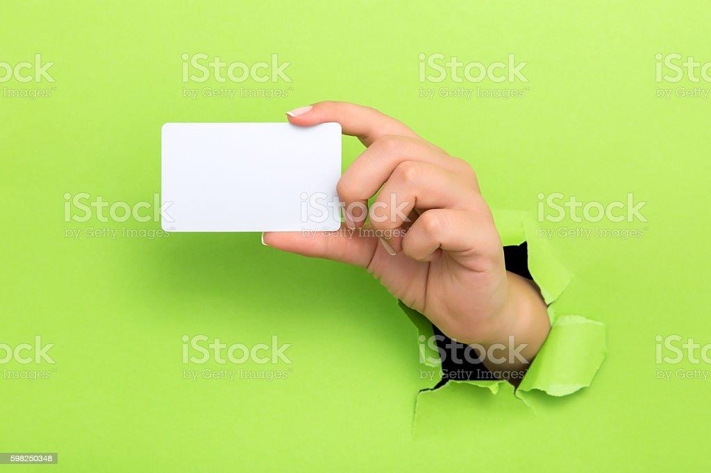 Female hand reaching through torn green paper sheet – Foto