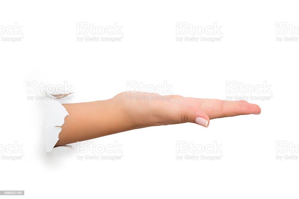 Female hand reaching through torn green paper sheet photo libre de droits