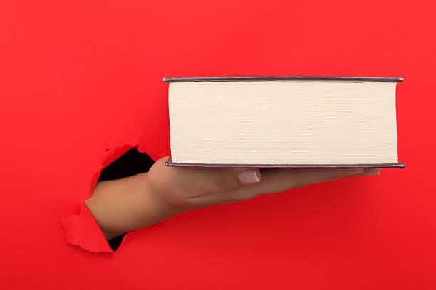 Female hand reaching through torn red paper sheet – Foto