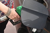 Female hand refilling the car with fuel on a filling station