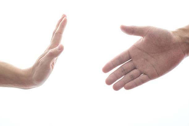 female hand refusing male hand to shake stock photo
