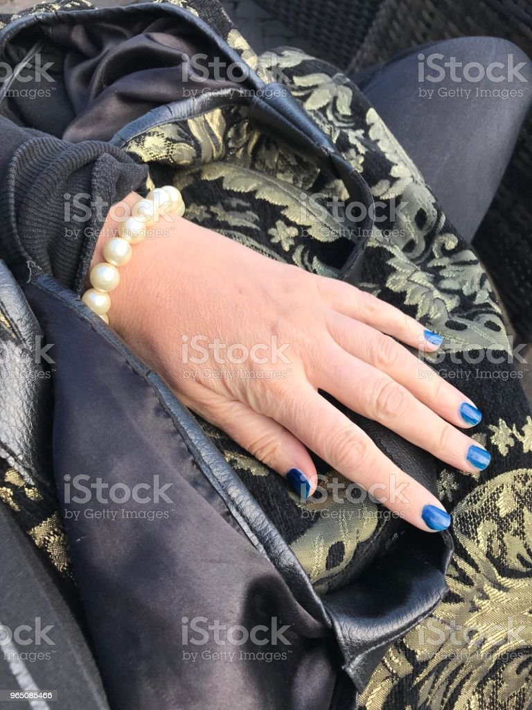 Female Hand Resting on a Brocade Bag royalty-free stock photo