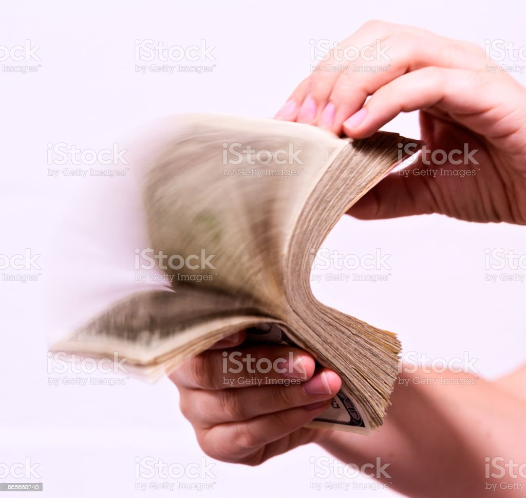 Female hand riffling through fistful of banknotes stock photo
